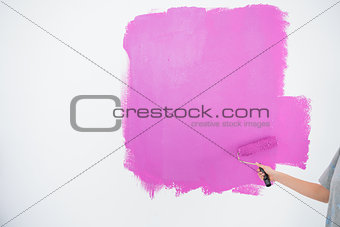 Woman painting her wall in pink