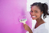 Happy young woman painting her wall in pink