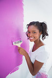 Cheerful young woman painting her wall in pink