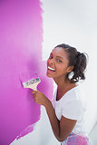 Laughing young woman painting her wall in pink