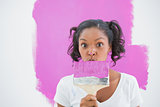 Happy woman making funny face behind paintbrush