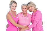 Happy women wearing pink tops and ribbons for breast cancer