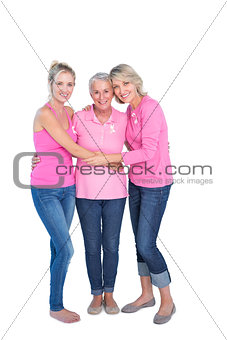 Smiling women wearing pink tops and ribbons for breast cancer