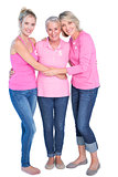 Cheerful women wearing pink tops and ribbons for breast cancer