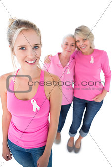 Three women wearing pink tops and breast cancer ribbons