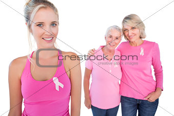 Three happy women wearing pink tops and breast cancer ribbons