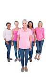 Diverse group of happy women wearing pink tops and breast cancer ribbons