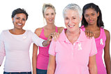 Supportive group of women wearing pink tops and breast cancer ribbons