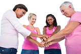 Smiling women wearing breast cancer ribbons putting hands together
