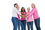 Women wearing breast cancer ribbons with hands together and smiling