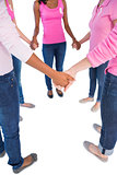 Women wearing pink and ribbons for breast cancer holding hands in a circle