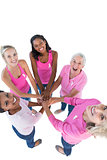Happy women wearing pink and ribbons for breast cancer putting hands together looking up at camera