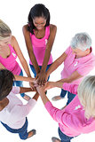 Group of women wearing pink and ribbons for breast cancer putting hands together