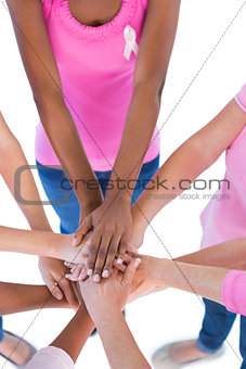 Group wearing pink and ribbons for breast cancer putting hands together
