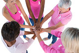 Group wearing pink and ribbons for breast cancer with hands together