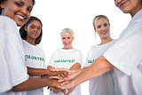 Team of female volunteers with hands together smiling at camera