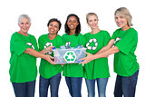 Team of happy female environmental activists holding box of recyclables