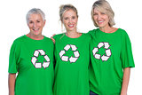 Three women wearing green recycling tshirts smiling at camera