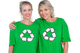 Two smiling women wearing green recycling tshirts