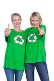 Two women wearing green recycling tshirts giving thumbs up