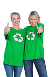 Two blonde women wearing green recycling tshirts giving thumbs up