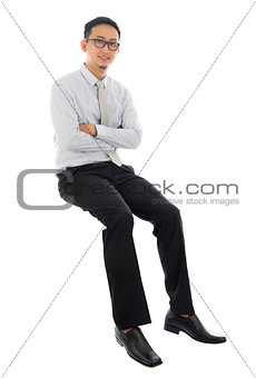 Asian businessman sitting on a transparent block