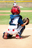 Young baseball catcher during game.