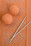 Orange balls, knitted pattern and knitting needles