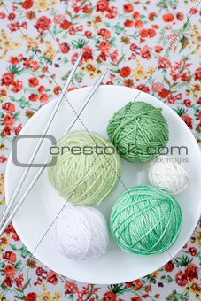 A lot of bright balls of knitting on the background of a red flower