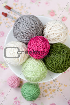 A lot of bright balls of knitting on the background of a pink flower