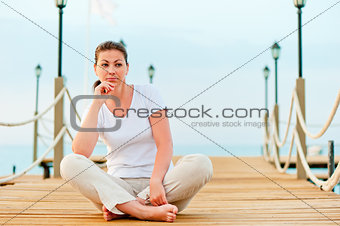 beautiful girl resting on a pier at dawn