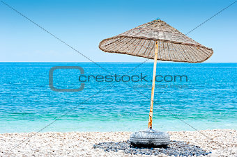lone wicker umbrella on the beach