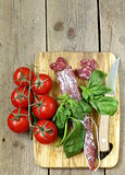 Still life of delicacy salami, tomatoes and basil -  rustic style