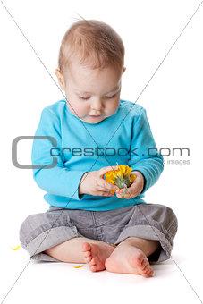 Small baby touching yellow flower