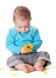 Small baby playing with yellow flower