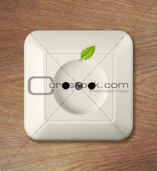 outlet on wooden wall with leaf. green power concept.