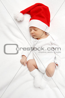 baby with Santa Claus hat sleeping on bed
