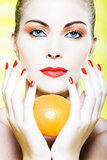Woman portrait holding a orange tangerine citrus fruit