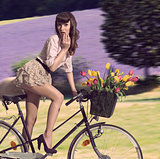 vintage woman on bicycle  with flowers