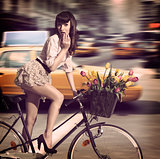 vintage woman on bicycle in a city street with taxi
