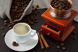 A cup of coffee near roasted coffee beans and a coffee grinder