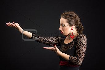 Portrait of spanish woman dancing flamenco on black