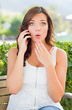 Shocked Young Adult Female Talking on Cell Phone Outdoors