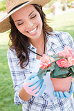 Young Adult Woman Wearing Hat Gardening Outdoors