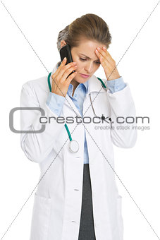 Concerned doctor woman talking mobile phone