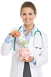 Smiling doctor woman putting euros banknote in piggy bank