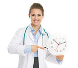 Smiling doctor woman pointing on clock
