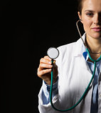 Doctor woman using stethoscope isolated on black