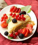 thin dessert pancakes (crepes) with various berries