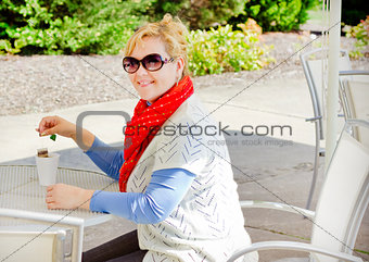 Smiling blond young woman drinking tea in a cafe